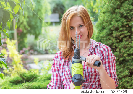 Long hair young woman is showing electric drill 58978093