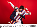 Young man and senior father with longboard in a studio on red background. 58979084