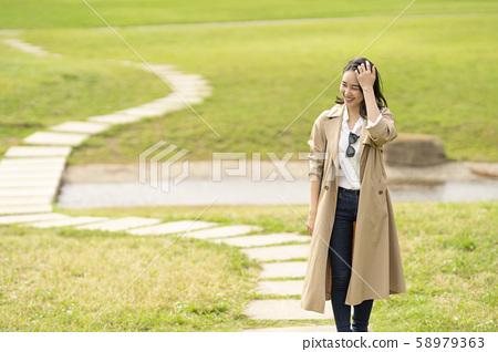 트렌치 코트를 입은 멋진 여성 58979363