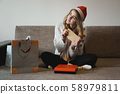 Beauty girl opening present gifts sitting on sofa at home 58979811
