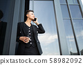 Young beautiful businesswoman posing against modern building 58982092