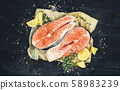 Salmon steaks on black background, top view, photo filtered in vintage style 58983239