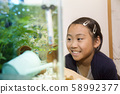 Elementary school girl looking at tropical fish 58992377