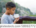 Asian kid boy is drinking water from the glass. 58992772