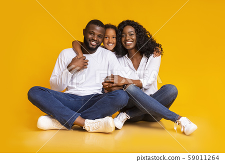 Happy black family embracing while sitting on floor together 59011264