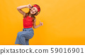 schoolgirl in a red T-shirt and jeans dancing energetically on a yellow background, emotional 59016901