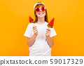 red-haired beautiful girl in a white T-shirt on a background of an orange wall, mockup, emotional 59017329