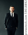 Portrait of elegant young man in suit on black background 59018892