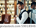 Young business man in dark elegant suit looking at his watch 59018946