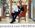 Confident young businessman reading newspaper and latest news while sitting in armchair 59018958