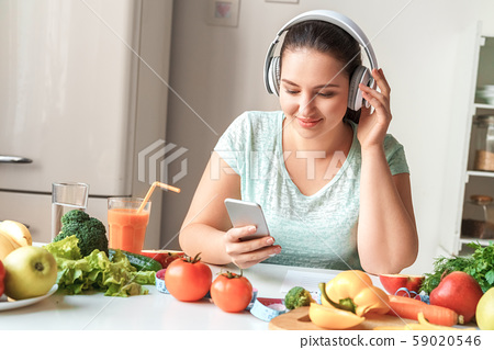 Body Care. Chubby girl in headphones sitting at kitchen table browsing playlist on smartphone 59020546