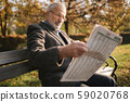 Handsome grandfather with a beautiful beard in a gray jacket sits on a bench in the park and reads a 59020768