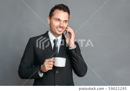 Businessman studio standing isolated on grey drinking coffee talking on smartphone smiling happy 59021295