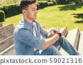 Outdoors Leisure. Stylish guy sitting on stairs in park checking time on wristwatch smiling happy 59021316