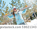 Winter vacation. Woman in goggles and helmet standing outdoors with skis smiling cheerful 59021343