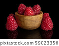 Fresh red raspberry isolated on black glass 59023356
