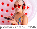 sexy blonde in a swimsuit listens to music with headphones on a white background 59029507