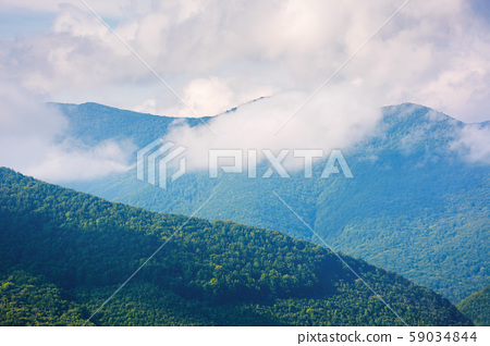 cloud above the forested hill 59034844