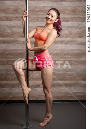 Woman doing pole dance in a dance studio 59035363