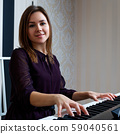 Young woman sitting and playing on the electronic piano 59040561