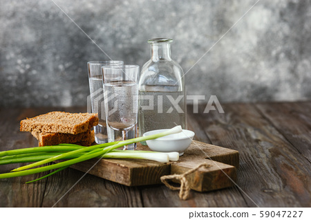 Vodka and traditional snack on wooden background 59047227