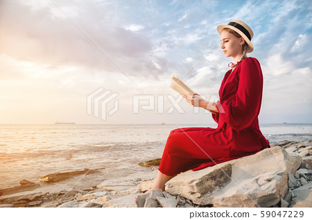 An attractive Caucasian girl in a red bright dress and a straw hat sits on a large stone by the sea 59047229