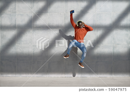 African Man Jumping For Joy Listening To Music 59047975