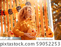 Halloween Preparaton Concept. Young woman standing outdoors with jack-o'-lantern smiling inspired 59052253