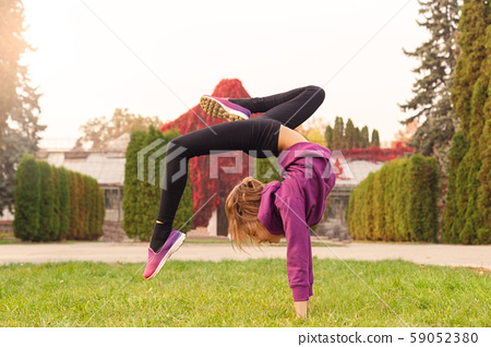 Outdoors leisure. Little gymnast doing backbend in the autumn park cheerful 59052380