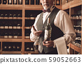 Sommelier Concept. Senior man standing with bottle and wine glass upside down serious close-up 59052663