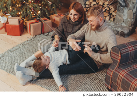 Young caucasian family mom dad son near fireplace christmas tree 59052904