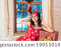 Beautiful woman in pajamas with gift box, window in the background. 59053014