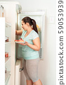 Body Care. Chubby girl standing in kitchen taking plate with desserts from fridge joyful side view 59053939