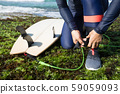 woman surfer tying leg leash with surfboard on 59059093