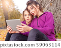 Outdoors leisure. Sisters sitting near tree in the autumn park with digital tablet watching video 59063114