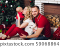 Happy family sitting near fireplace with little 59068864