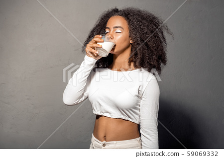 Freestyle. African girl in white outfit with bare belly standing isolated on gray drinking milk 59069332