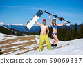 Sexy skier woman in bikini and snowboarder man with bare torso on background of snowy mountains. 59069337