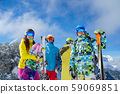 Three men and woman with snowboard and skis standing on snowy resort against background of mountain 59069851