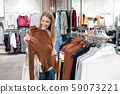 Happy girl holding brown turtleneck while standing by rack of new collection 59073221
