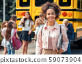 Classmates going to school by bus african girl close-up with book smiling cheerful 59073904