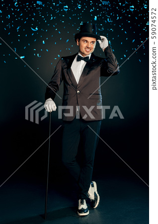 Professional Occupation. Showman in suit gloves and hat standing isolated on wall with cane posing 59074572
