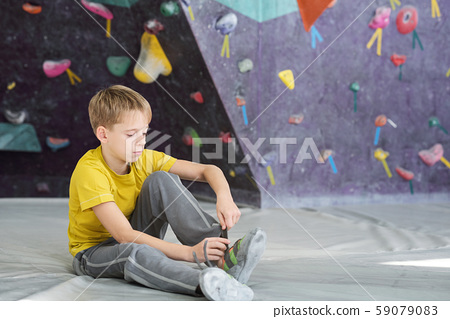 Schoolboy in activewear sitting on the floor in sports club and tying shoelace 59079083