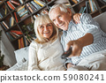 Senior couple together at home retirement concept watching tv switching channels 59080241