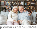 Senior couple together at home retirement concept watching tv holding remote controller 59080244