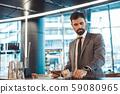 Businessman standing at a business center bar counter paying bill 59080965
