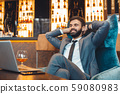 Businessman sitting in a business center bar watching movies 59080983