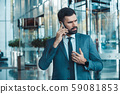 Businessman in a fromal suit in a business center smartphone call 59081853