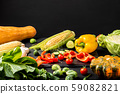 Chopped vegetables on a black board and different fresh vegetables on a black table. 59082821