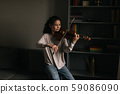 Beautiful young woman violinist plays the violin at home 59086090